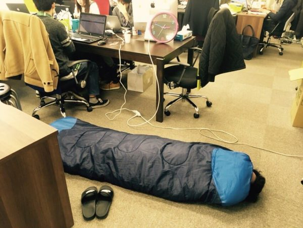 オフィスで寝袋にくるまる社員