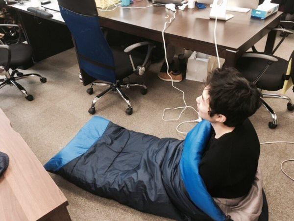 寝袋のなかで正座する社員